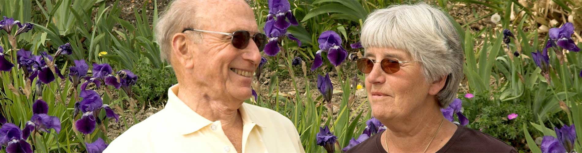 Man and woman both wearing glasses and smiling at each other in front of a bed of purple flowers.
